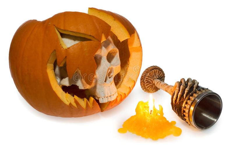 Halloween ghost human skull comes out of a broken pumpkin, scary. Goblet decorated with bones. Skeleton head and bowl decorated with skeleton hand and skulls royalty free stock photos