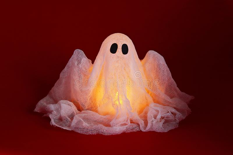 Halloween ghost of starch and gauze on orange background. Gift idea, decor Halloween stock photos