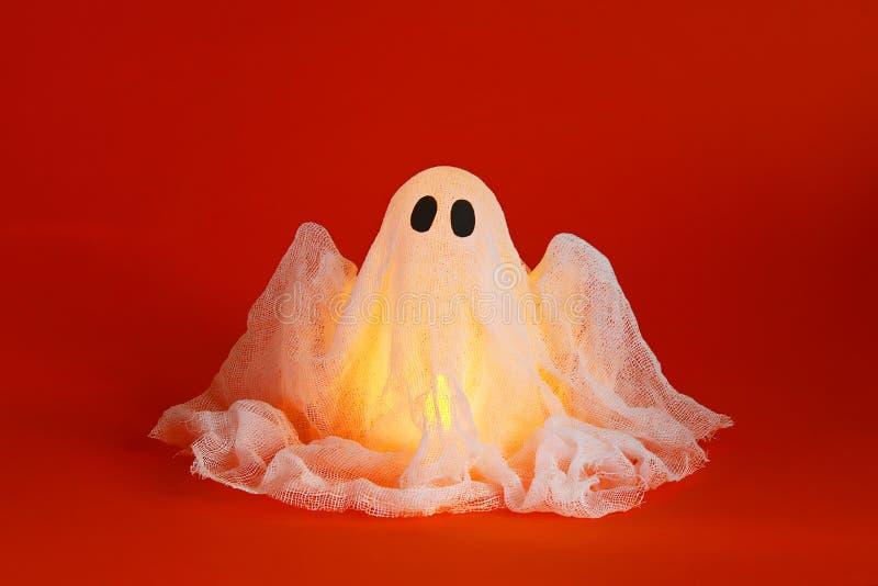 Halloween ghost of starch and gauze on orange background. Gift idea, decor Halloween stock image