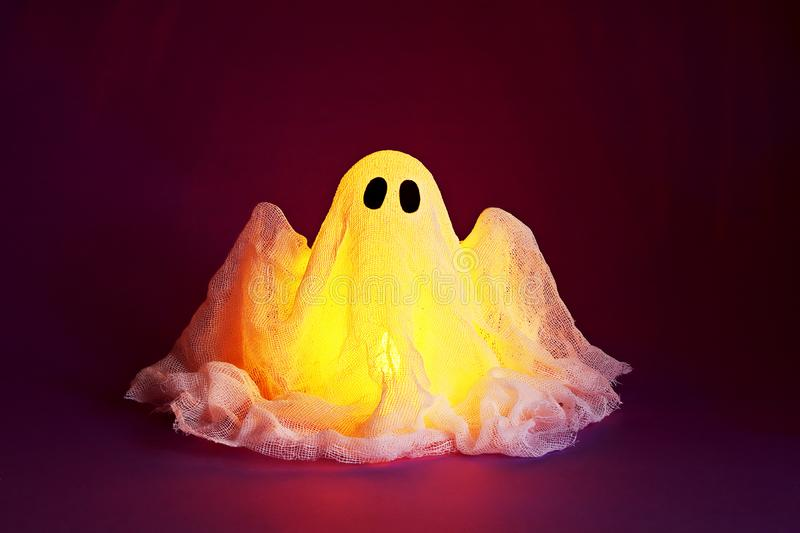 Halloween ghost of starch and gauze on ultraviolet background. Gift idea, decor Halloween royalty free stock photography