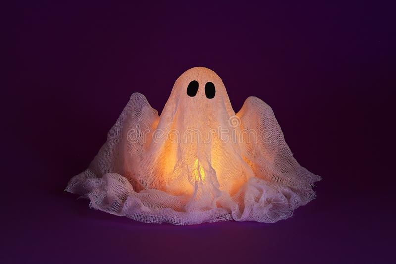 Halloween ghost of starch and gauze on ultraviolet background. Gift idea, decor Halloween stock photo