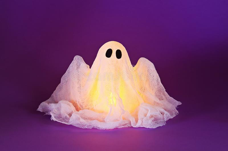 Halloween ghost of starch and gauze on ultraviolet background. Gift idea, decor Halloween royalty free stock images