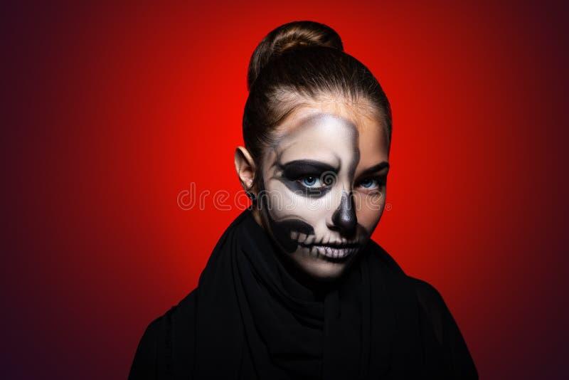 Halloween giovane bella ragazza con trucco di scheletro sul suo fronte Ragazza su un fondo rosso luminoso fotografie stock libere da diritti