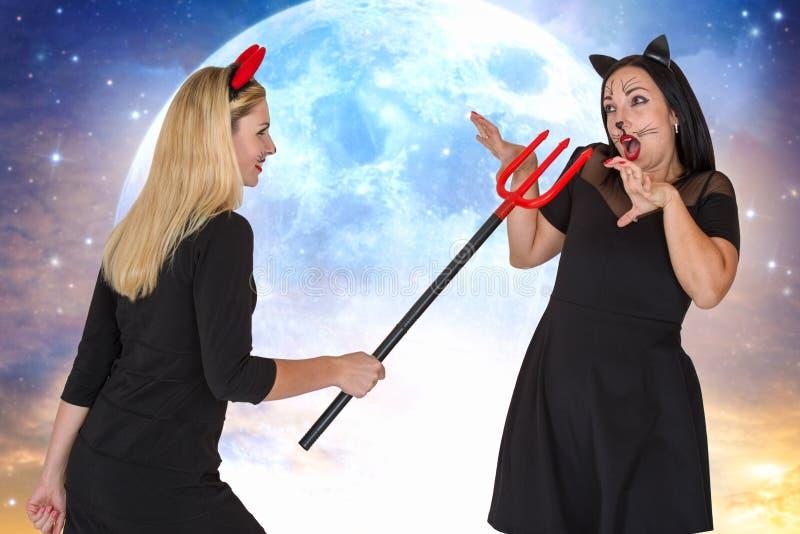 Halloween Giovane donna due in costumi di Halloween che spaventano Trident immagine stock libera da diritti