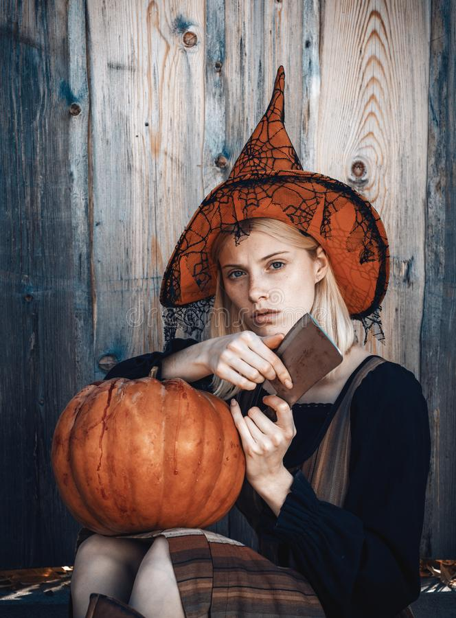 Halloween girl. Attractive witch holding pumpkin and knife for a `trick or treat`. Woman dressing in Halloween costume royalty free stock photo