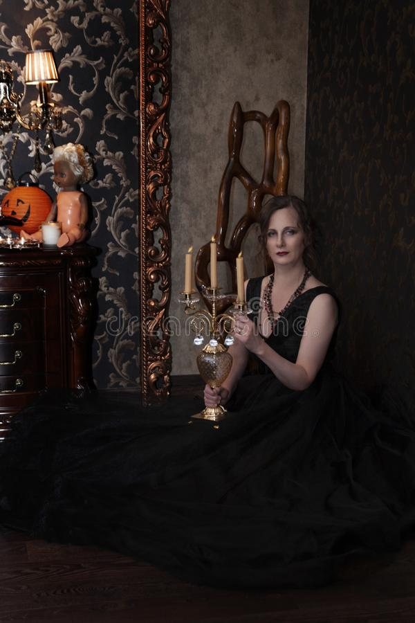 Woman in black dress for Halloween. Halloween, a girl in a black dress in a Gothic environment in a dark room, causes fear. woman in black dress for Halloween royalty free stock photos