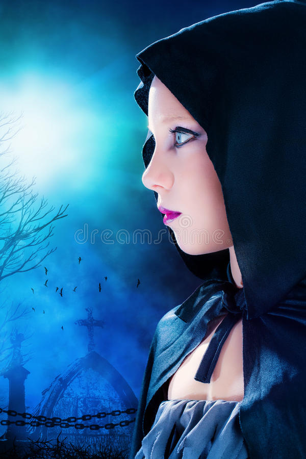 Halloween girl with graveyard in background. stock photo