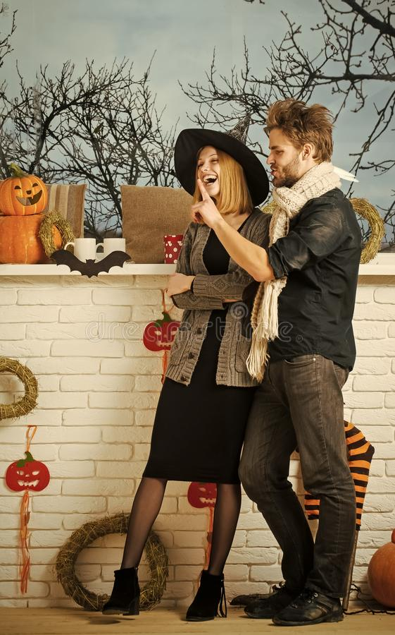Halloween girl and macho talking and smiling at window. Woman in witch hat. Man wearing knitted scarf. Couple in love, family and relationship concept. Happy royalty free stock image