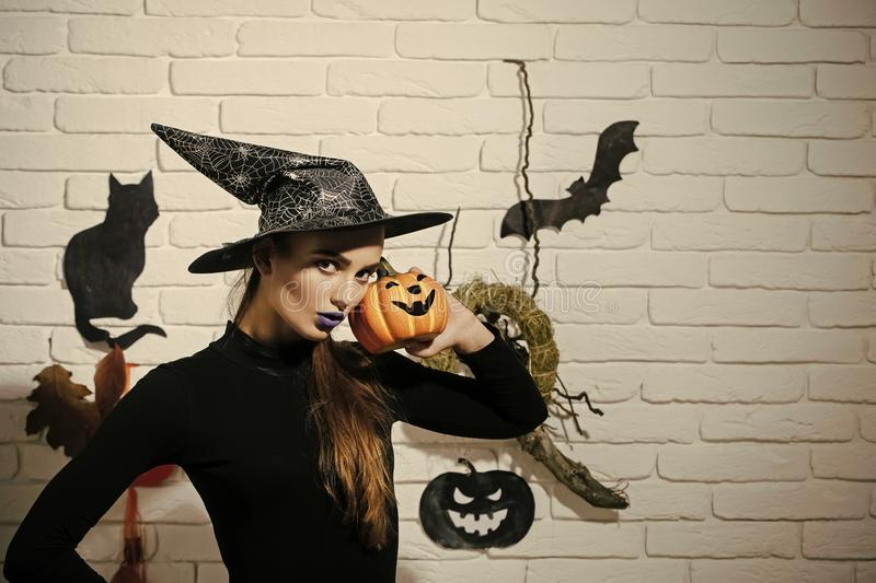 Halloween girl in witch hat and black costume. Woman with blue lips and pumpkin. Jack o lantern. Mystery and horror concept. Holiday celebration symbols on stock images