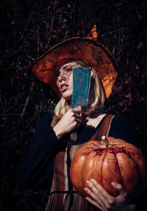 Halloween girl. Woman dressing in Halloween costume with orange witch`s hat for a themed party. Attractive witch holding stock photos