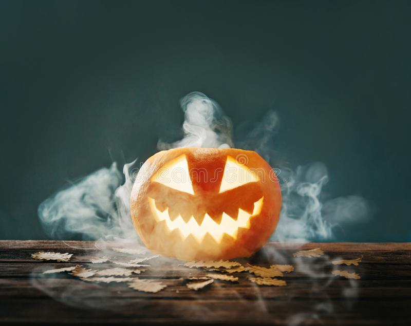Halloween jack-o-lantern pumpkin with smoke. Halloween glowing jack-o-lantern pumpkin with smoke or fog on wooden table with autumn leaves royalty free stock photos