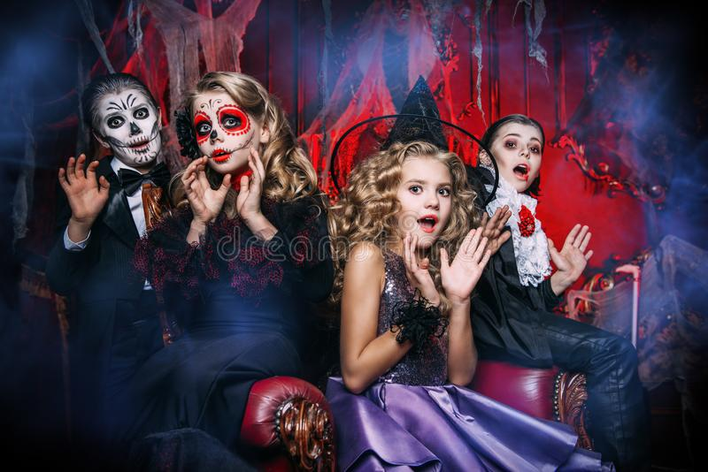 Party in the castle. Halloween. Group of children in carnival costumes in the old castle stock photography
