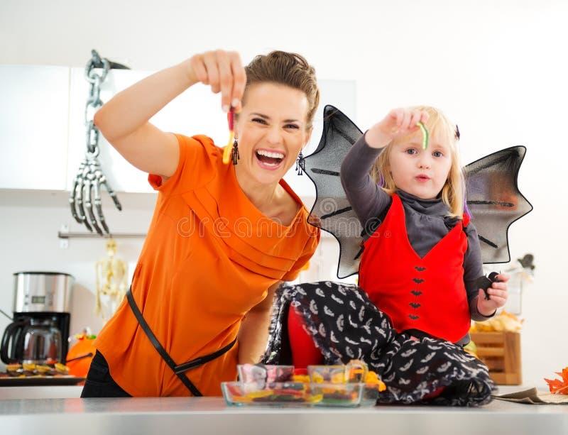 Halloween a habillé la fille avec la mère montrant les sucreries gommeuses de ver photo libre de droits