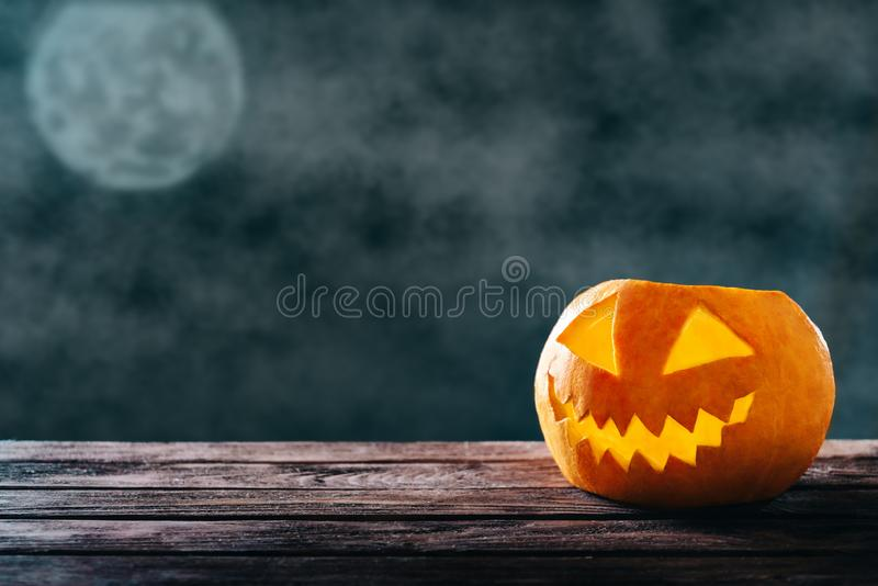 Halloween happy pumpkin in dark night. Halloween happy pumpkin lantern on background of dark night and full moon royalty free stock images
