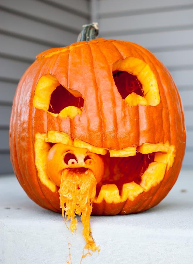 Halloween-hefboom-o-lantaarn met een andere hefboom-o-lantaarn in zijn mond met pompoen die van kleine de hefboom-o-lantaarns mon stock afbeeldingen