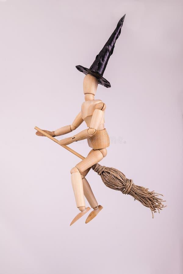 Halloween-heks die een bezem berijden die een zwarte gerichte heksenhoed dragen op stevige achtergrond royalty-vrije stock fotografie