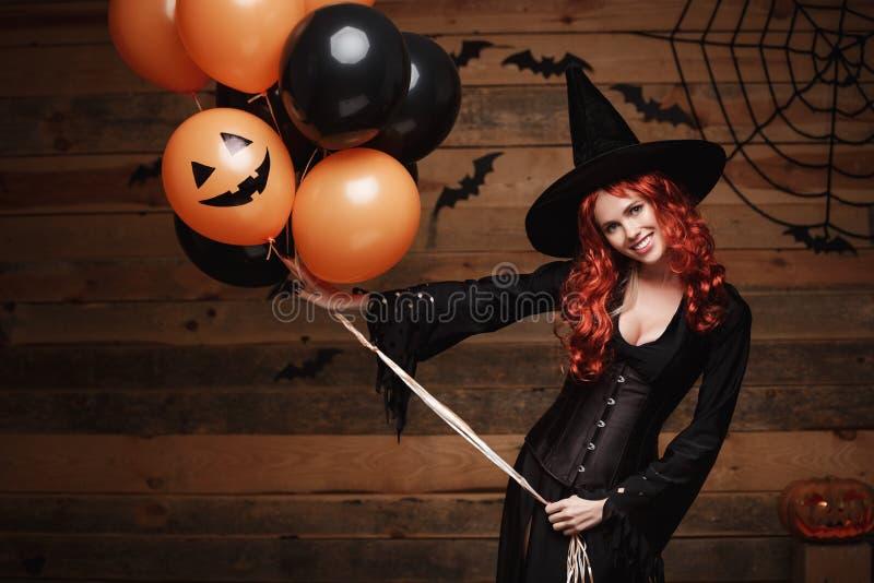 Halloween-Heksenconcept - Mooie Kaukasische vrouw die in heksenkostuums Halloween-het stellen met het stellen met sinaasappel en  stock foto