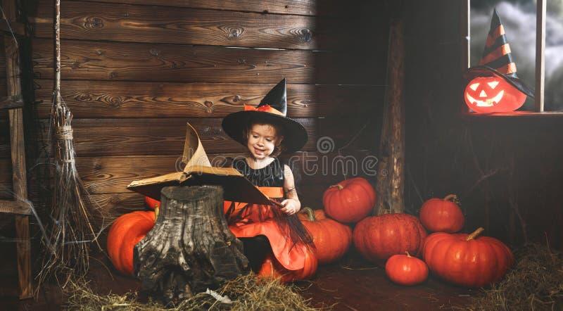 Halloween het heksenkind tovert met boek van werktijden, toverstokje en pompoenen stock afbeeldingen