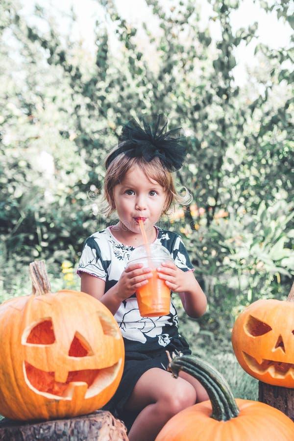 Halloween Het kind gekleed in zwarte het drinken pompoencocktail, truc of behandelt Het meisje dichtbij hefboom-o-lantaarn decora royalty-vrije stock fotografie