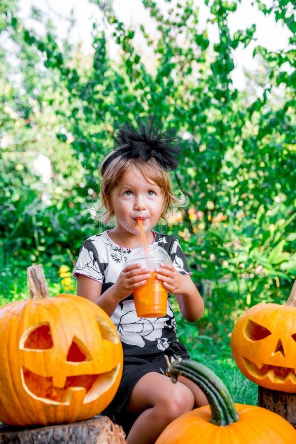 Halloween Het kind gekleed in zwarte het drinken pompoencocktail, truc of behandelt Het meisje dichtbij hefboom-o-lantaarn decora royalty-vrije stock afbeeldingen