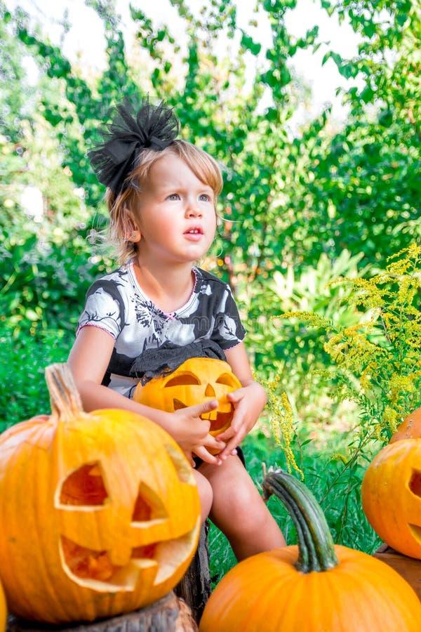 Halloween Het kind gekleed in zwarte met in hand hefboom-o-lantaarn, de truc of behandelen Meisjepompoen in het hout, in openluch royalty-vrije stock afbeeldingen