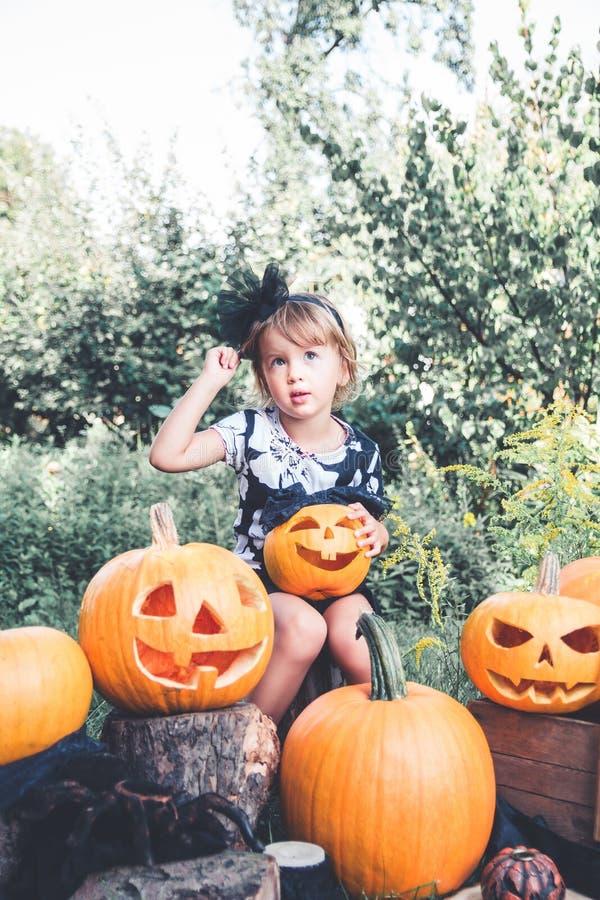 Halloween Het kind gekleed in zwarte met in hand hefboom-o-lantaarn, de truc of behandelen Meisjepompoen in het hout, in openluch stock foto