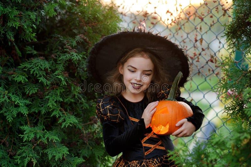 Halloween Het meisje is gekleed in donkere kleding en hoed stock afbeeldingen