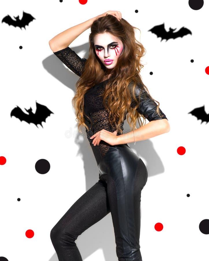 Halloween Het sexy meisje van de vakantiepartij Mooie jonge vrouw met heldere vampiermake-up en het lange haar stellen in heksenk royalty-vrije stock afbeeldingen