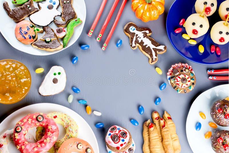 Halloween-het snoepje behandelt, het concept van het partijvoedsel Enge koekjes, monsterkoekjes en vruchten op grijze achtergrond stock foto's