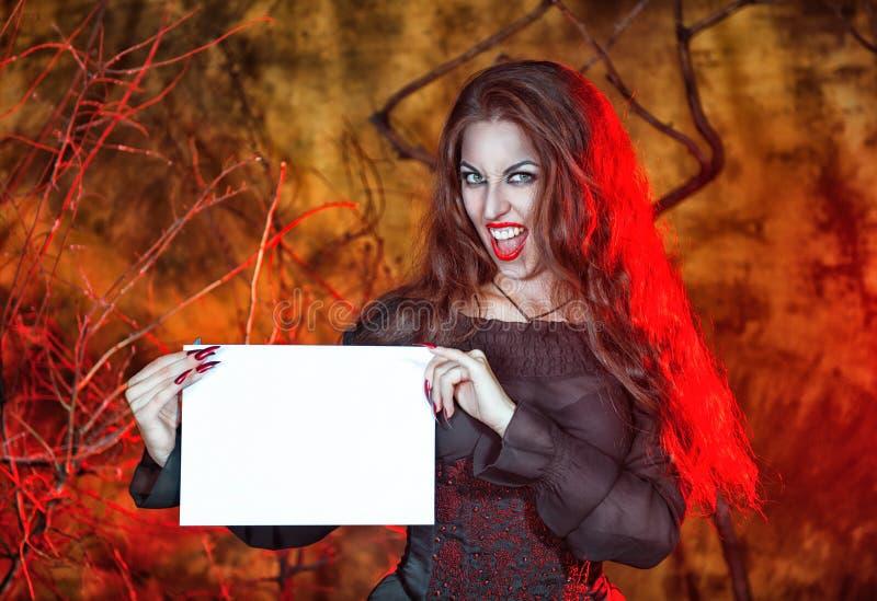 Halloween-Hexe, die Blatt Papier hält lizenzfreie stockfotografie
