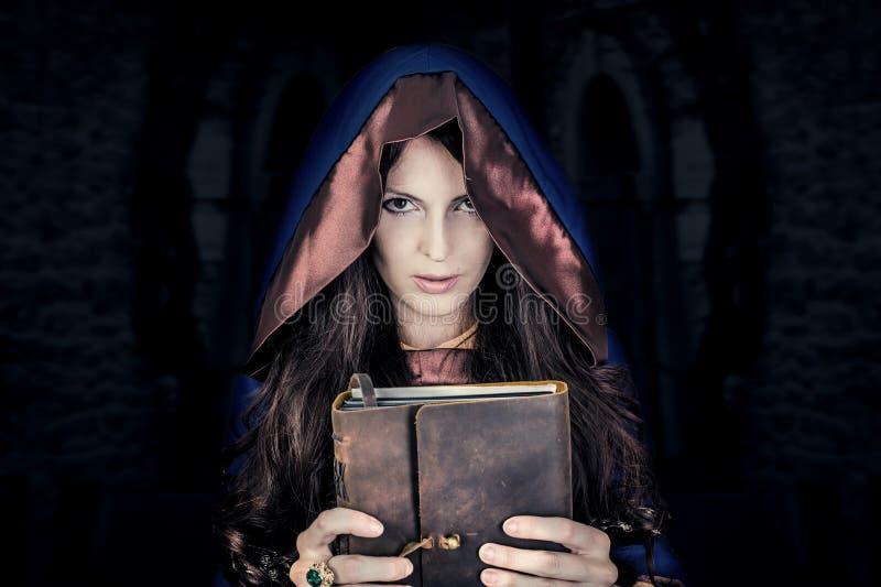 Halloween-Hexe, die magisches Buch von Bannen hält lizenzfreie stockbilder