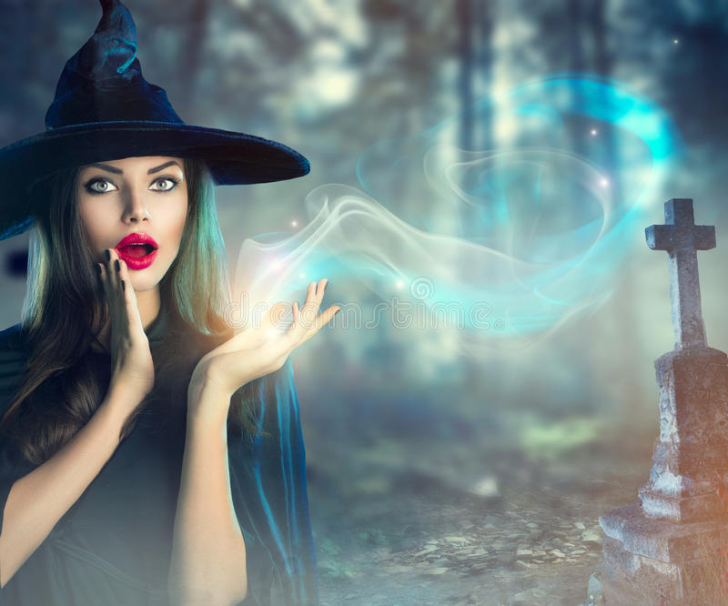 Halloween-Hexe an einem dunklen alten gespenstischen Kirchhof stockfoto
