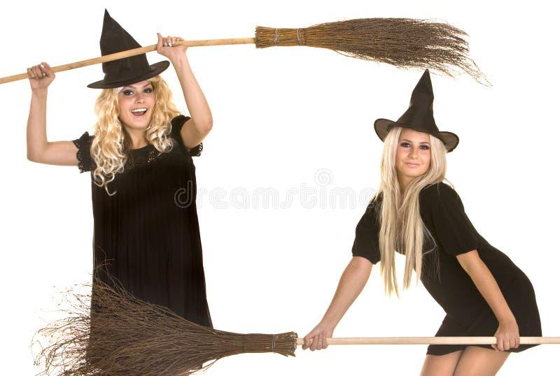 Halloween-Hexe im schwarzen Hut auf Besenfahne. stockfotografie