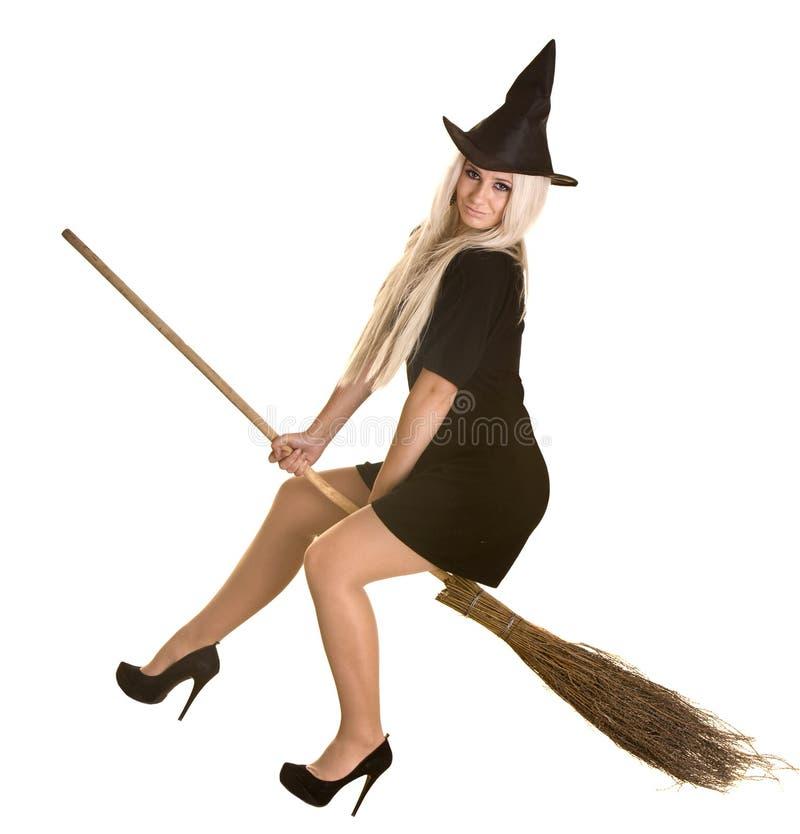 Halloween-Hexe im schwarzen Kleid und im Hut auf Besen. stockfoto