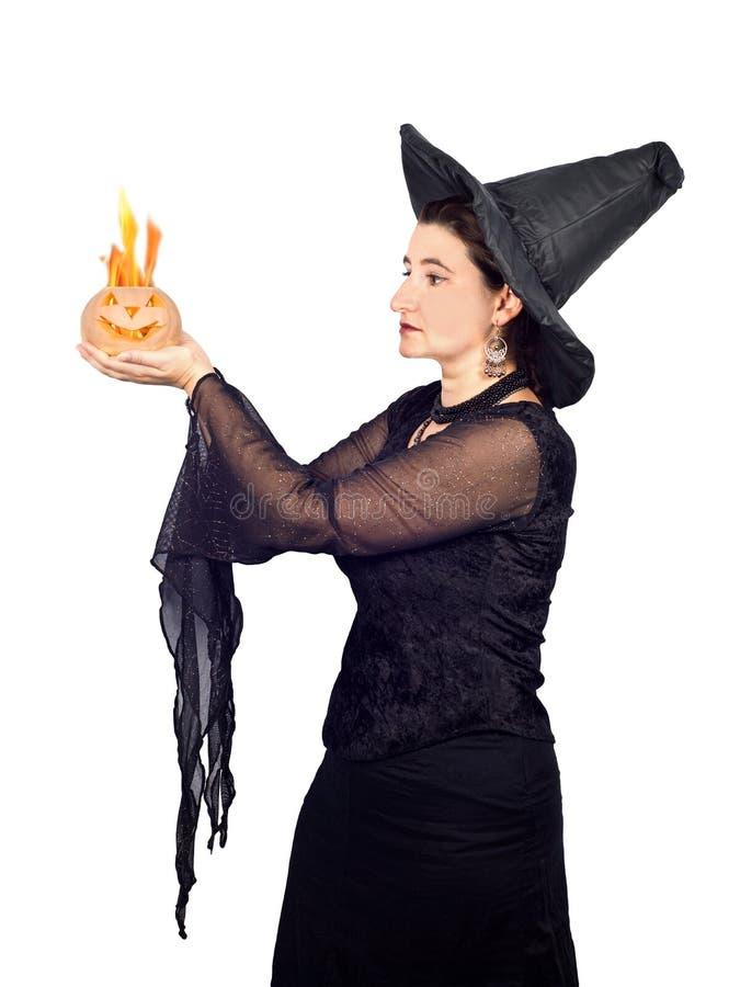 Halloween-Hexe mit brennendem Kürbis stockbilder