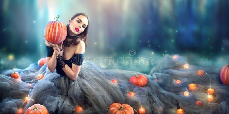 Halloween-Hexe mit einem geschnitzten Kürbis und einer Magie beleuchtet in einem Wald lizenzfreies stockbild
