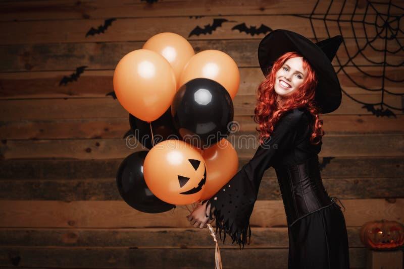Halloween-Hexen-Konzept - schöne kaukasische Frau in der Hexe kostümiert das Feiern von Halloween, das mit der Aufstellung mit Or lizenzfreie stockfotos