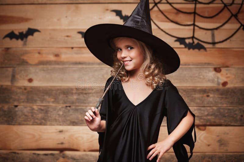 Halloween-Hexenkonzept - kleines Hexenkind genießen, mit magischem Stab zu spielen über Schläger- und Spinnennetzhintergrund stockbilder