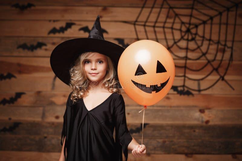 Halloween-Hexenkonzept - kleines kaukasisches Hexenkind genießen mit Halloween-Ballon über Schläger- und Spinnennetzhintergrund lizenzfreie stockfotografie