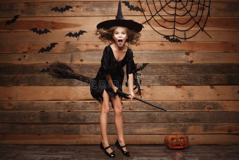 Halloween-Hexenkonzept - kleines kaukasisches Hexenkinderfliegen auf magischem Besenstiel über Schläger- und Spinnennetzhintergru lizenzfreies stockbild