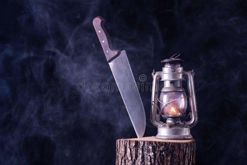 Halloween-Hintergrund der großen Lampe des Messers und alten des Öls des Burning auf hölzernem Anmeldungswald lizenzfreie stockfotografie