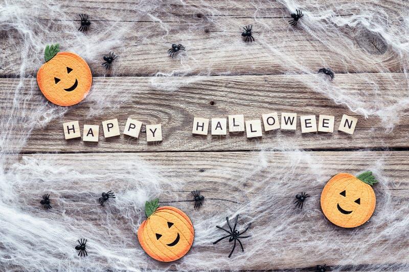 Halloween-Hintergrund mit dekorativen Kürbisen, gruseligem Netz und Spinnen auf alten hölzernen Brettern stockfotografie