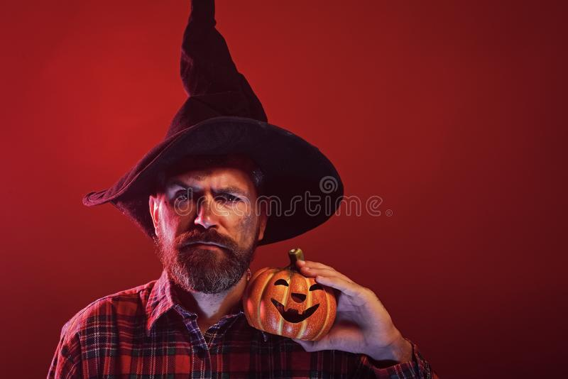 Halloween hipster in wizard hat holding pumpkin. On red background. Man with beard and jack o lantern. Autumn holiday celebration. Trick or treat. Mystery and royalty free stock photos