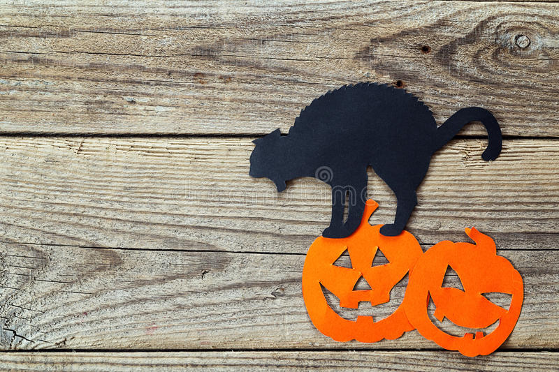 Halloween holiday background with black cat and Jack-o'-Lantern cut paper on old boards. Space for text stock images