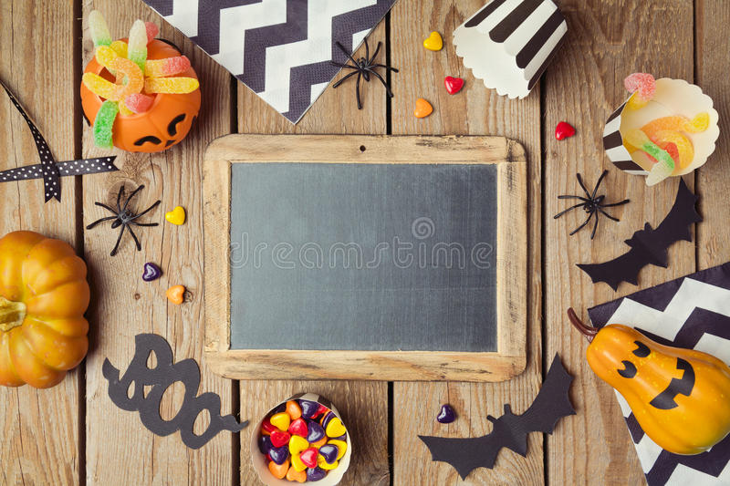 Halloween holiday background with chalkboard, pumpkin and candy. stock photo