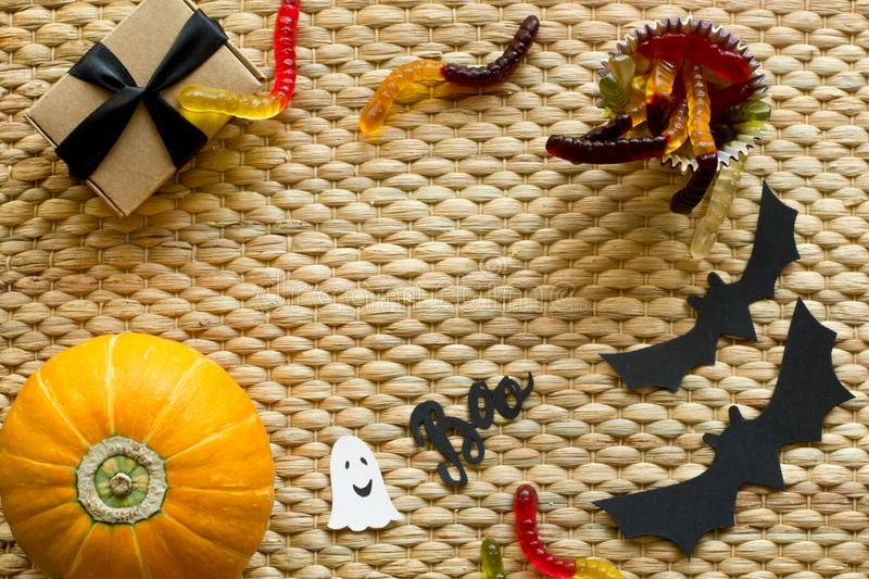 Halloween holiday background with pumpkin, worm candy, ghost, bat, gift box stock image