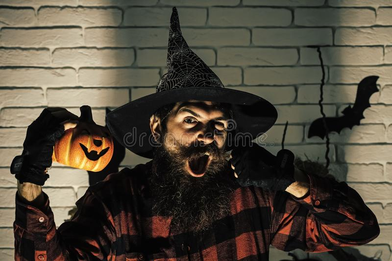Halloween holiday celebration symbols on brick wall. Hipster with beard shouting in witch hat and plaid shirt. Man with pumpkin in dark shadow. Jack o lantern stock image