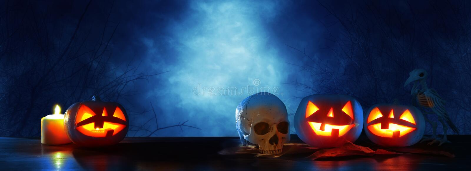 Halloween holiday concept banner. Pumpkins over wooden table at night scary, haunted and misty forest. stock images
