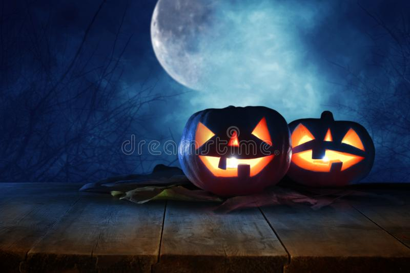 Halloween holiday concept. Empty rustic table in front of Pumpkins over wooden table at night scary, haunted and misty forest. Rea. Dy for product display stock photo