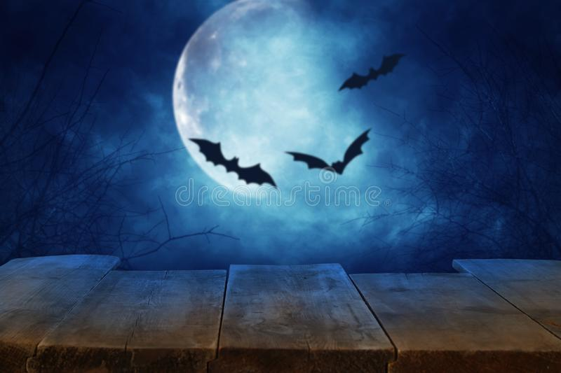 Halloween holiday concept. Empty rustic table in front of scary and misty night sky with black bats and full moon background. Read. Y for product display montage stock photo